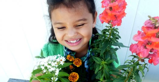 A smiling child surrounded by flowers