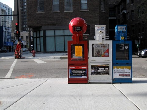 Newspaper dispensers on a sidewalk