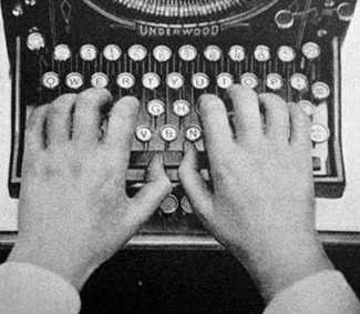 A pair of hands typing on a typewriter